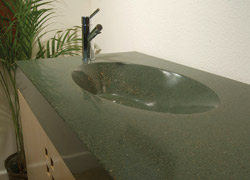 Deep green pigmented concrete countertop with sink cast in place, faucet on the end of the countertop.