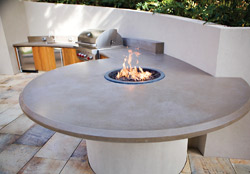 Concrete outdoor fire pit in the center of an outdoor table attached to an retaining wall.