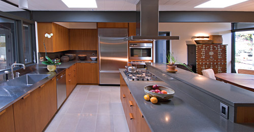Modern kitchen with deep gray precast concrete countertops and stainless steel appliances.