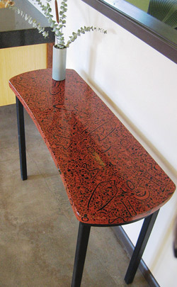 Long sofa table made of precast concrete countertop in a deep red with black swirls and specks.
