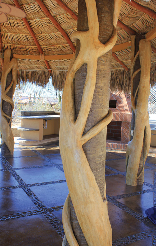 Concrete pillar that holds up the roof has a tree root carved out of concrete wrapped around it.