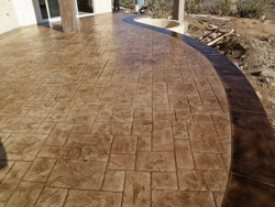Stamped concrete deck with dark brown ban surround.