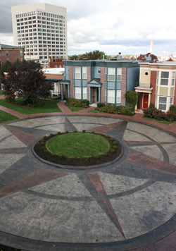 A large compass rose with a planter in the middle on an outdoor courtyard.