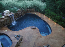 A unique pool with a stamped concrete pool deck nestled in the greens of the forest.