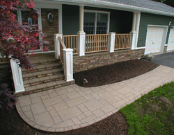 All of the vertical areas of the deck, as well as portions of the house and garage, were then covered using cultured stone. By enclosing the area underneath the deck and covering it in stone, we were able to create the illusion of a masonry porch.