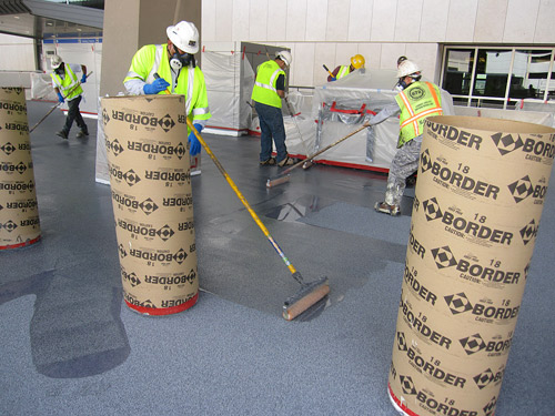 Concrete contractors installing an overlay to the floors of the terminal at McCarran International