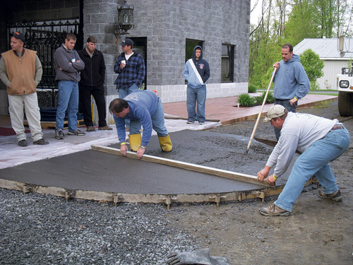 Bart Sacco and a crew screed freshly poured concrete with a piece of wood.