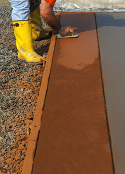 A person in yellow rain boots trowels a slab of integrally colored concrete.