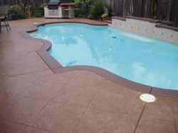 Wayne Morse of AM Resurfacing colored this pool deck with NewLook International's Original Solid Color Stain in Caramel and Translucent Color Enhancer in Oak. The bands are Original Solid Color Stain in Oak. Photo courtesy of NewLook International
