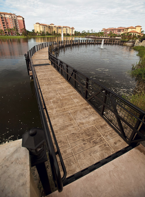 A stamped concrete walkway that stretches across the water in this open space in the city.