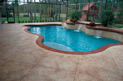 Stamped and stained pool deck with a net constructed around to keep the bugs out.