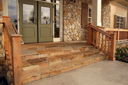 Stained steps in natural browns leading up to green double doors on this house.