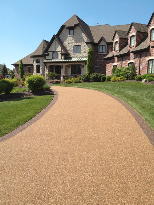 an expansive driveway leading up to a large home. the driveway has been finished with an Epoxy-Bonded Stone System