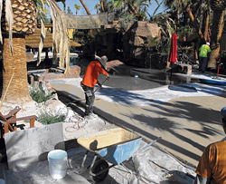 installing backyard concrete in a beachy tropical way.