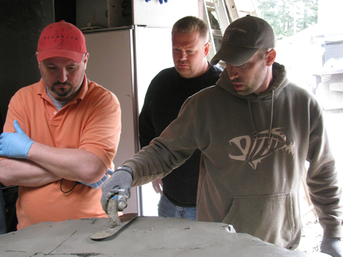 Three men work on a concrete piece with a trowel at the training workshop.