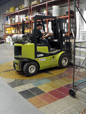 Forklift moving over the top of polished and dyed concrete floor.